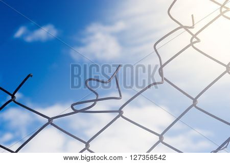 Broken Wire Fence And Blue Sky Background