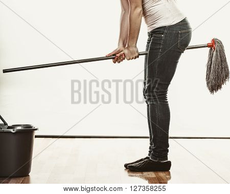 Closeup of human cleaning mopping floor having fun. Person with mop and bucket at home. House cleanup.