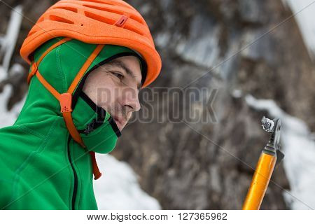 Man in orange helmet looking at ice axe on rock and ice background