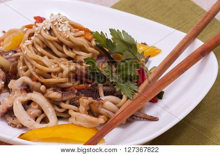 pasta with seafood and vegetables on a white plate with chopsticks