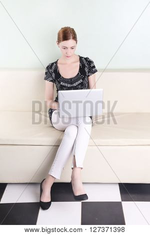 Young pretty woman sitting with laptop in her lap