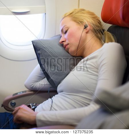 Tired blonde casual caucasian lady listens to music while napping on uncomfortable seat while traveling by airplane. Commercial transportation by planes.