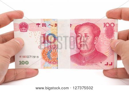 hand holding stacks of 100 RMB paper currency on white with clipping path