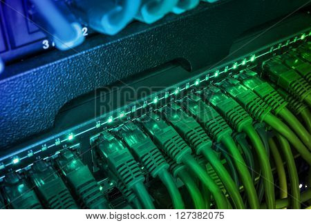 Close up of green network internet cables patch cords connected to black switch router in data center glowing in the dark