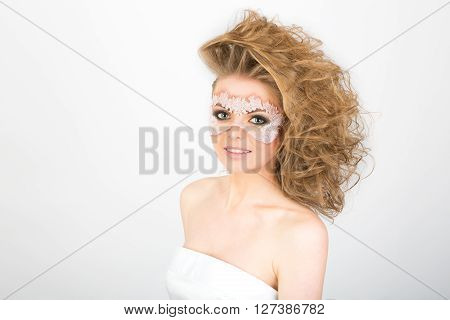 Crazy hairstyle and white lace mask on the face