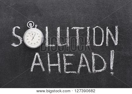 solution ahead phrase handwritten on chalkboard with vintage precise stopwatch used instead of O