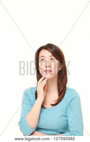 Japanese woman thinks about something on white background