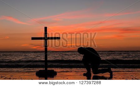 Man kneeling down at a beach in prayer as the sun colors the sky.