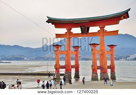 HIROSHIMA, JAPAN - APRIL 11, 2014: Many unidentified people visit famous great Torii gate at Itsukushima island in Hiroshima, Japan. This island is popularly known as Miyajima.