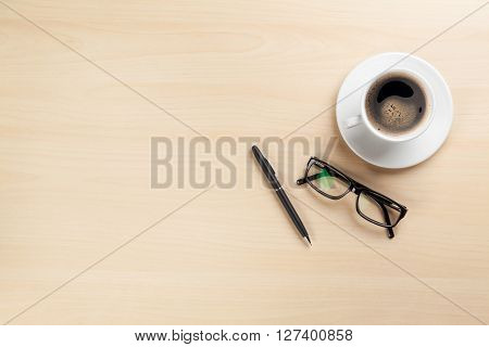 Office desk table with coffee cup, pen and glasses. Top view with copy space