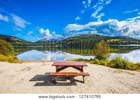 Early morning on cold Pyramid Lake, Jasper National Park. On the shore of the lake -  table and benches for picnic
