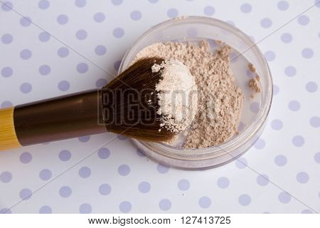 mineral Makeup powder and a powder brush on a purple background soft bedding colors close up