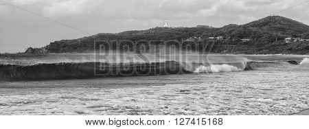 Black and white image of Byron Bay beach and waves in New South Wales, Australia with Cape Byron lighthouse in the background.