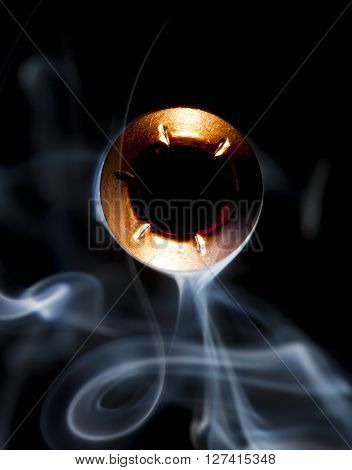 Hollow point bullet pointed at the camera with smoke around
