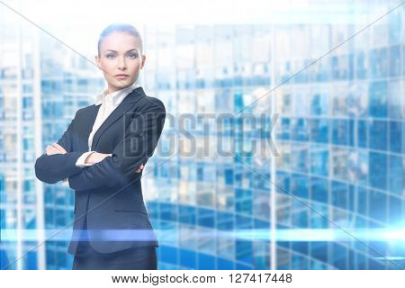 Portrait of businesswoman with hands crossed, on blue background. Concept of leadership and success