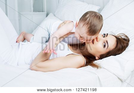 happy beautiful mother with her one year old son, studio shot