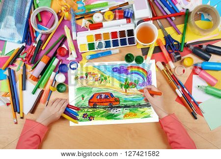 child drawing dog travel in car , top view hands with pencil painting picture on paper, artwork workplace