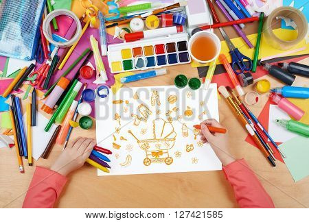 child drawing baby stuff - pram, wear and toys, top view hands with pencil painting picture on paper, artwork workplace