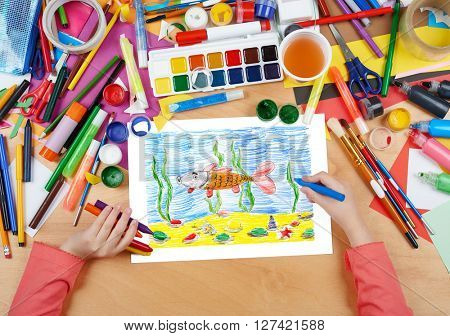 child drawing fish underwater and seabed, top view hands with pencil painting picture on paper, artwork workplace
