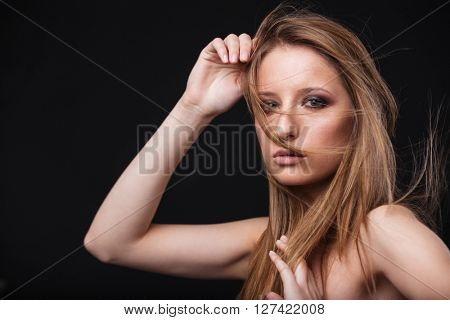 Beauty portrait of a young woman with fresh skin looking at camera over black background