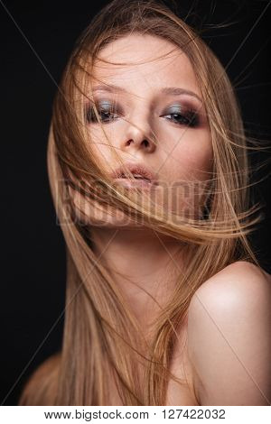 Beauty portrait of a lovely woman with fresh skin looking at camera over black background