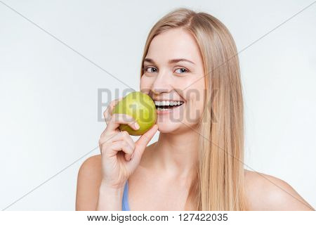 Cheerful woman holding apple and looking at camera isolated on a white background
