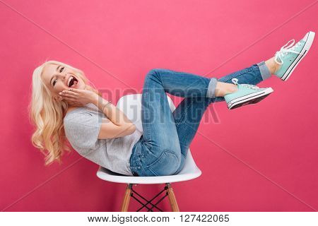 Laughing woman sitting on the chair with raised legs over pink backgorund