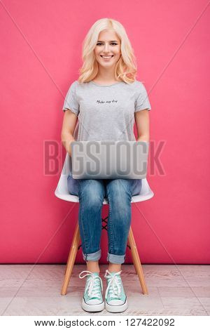 Smiling attractive woman sitting on the chair with laptop computer on pink background
