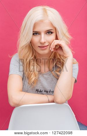 Happy cute woman looking at camera over pink background