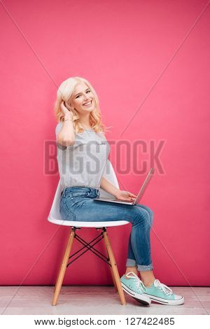 Pretty woman sitting on the chair with laptop computer over pink background