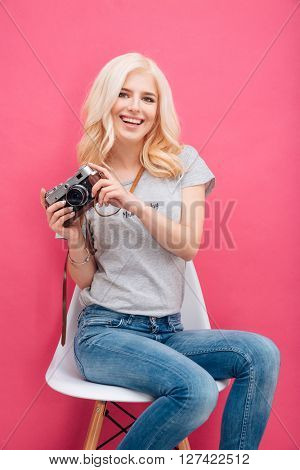 Happy charming woman holding photo camera over pink background
