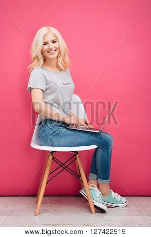 Smiling woman using laptop computer on the chair over pink background and looking at camera