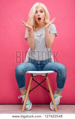 Amazed charming woman sitting on the chair over pink background