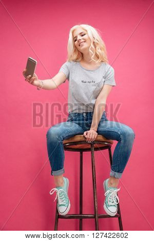 Smiling blonde woman making selfie photo on smartphone over pink background