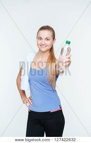 Happy sports woman with towel holding bottle with water isolated on a white background