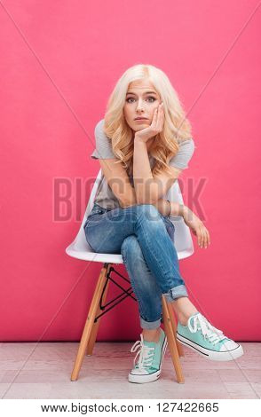 Sad young woman sitting on the chair over pink background
