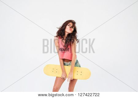 Lovely woman posing with skateboard isolated on a white background