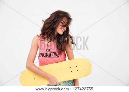 Happy relaxed woman posing with skateboard isolated on a white background