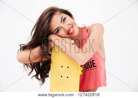 Cheerful woman with skateboard looking at camera isolated on a white background