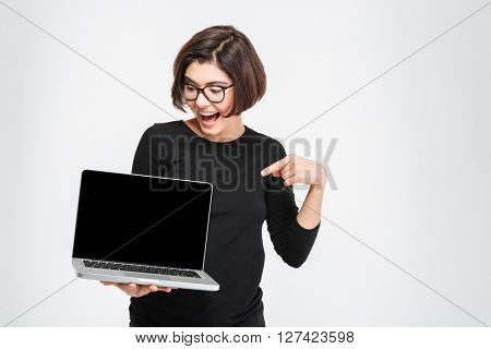 Cheerful woman pointing finger on blank laptop computer screen isolated on a white background