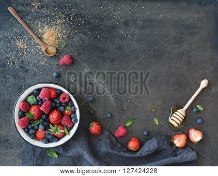 Berry frame with copy space on right. Strawberries, raspberries, blueberries and mint leaves, honey, cane sugar, dark grunge background, top view, copy space