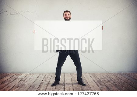 Handsome smiling young man holding blank horizontal white banner. Place for text.