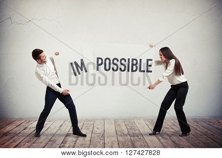 """Smiling businessman and businesswoman vigorously tearing the poster with the word """"impossible"""" into two parts """"im"""" and """"possible"""", trying to show that you can do this"""