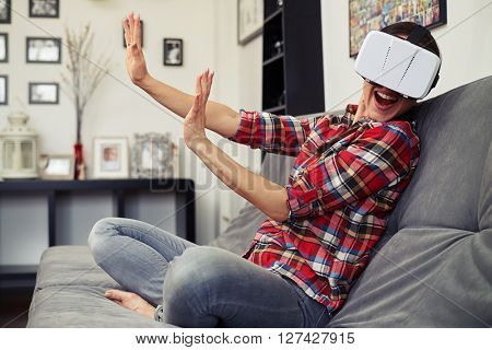 Woman repels someone in virtual reality and sitting on the couch