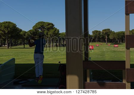 golf player practicing  shot with club on training course