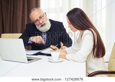 Young businesswoman and senior man with beard working and planning in the meeting