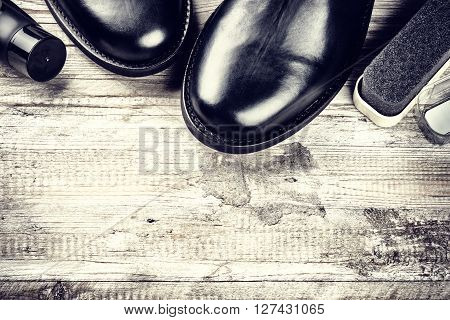 Black boots and shoe care accessories on wooden background. Copy space