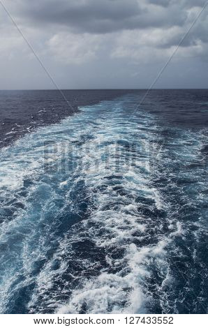 The wake of a cruise ship flows from the rear of the ship in the Caribean Sea