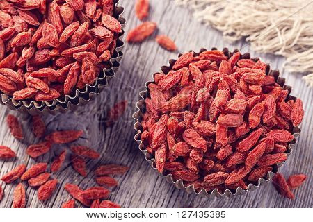 Goji berries in a bowl on a wooden background