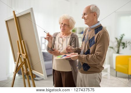 Senior couple drawing together on a canvas and looking at the painting at home